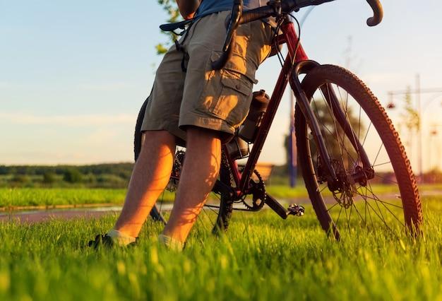 サイクリストは砂利の自転車に座って芝生の上で休みます。