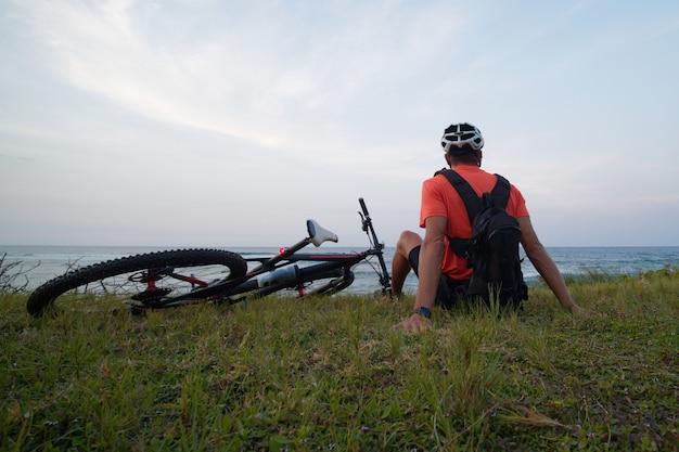 배낭을 메고 바다를 바라보며 자전거를 타고 잔디에 앉는 자전거 타는 사람. 뒷모습.