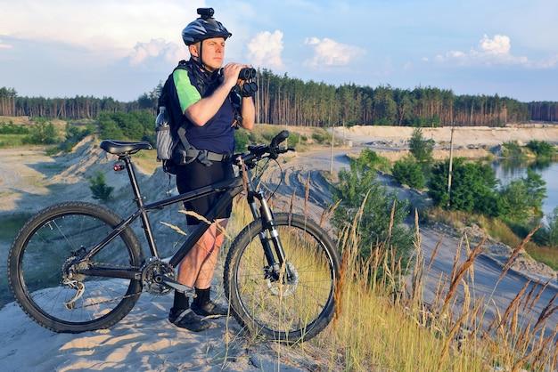자전거와 쌍안경을 손에 든 자전거 타는 사람은 햇빛 아래 모래 언덕에 서 있다