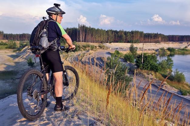자전거를 타는 사이클리스트는 햇빛 아래 모래 언덕에 있습니다.