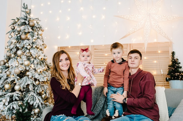お父さん、お母さんはクリスマスツリーの近くのソファに座っている幼い息子と娘を保持しています。メリークリスマス。クリスマスに飾られたインテリア。家族の冬休みの概念。閉じる。