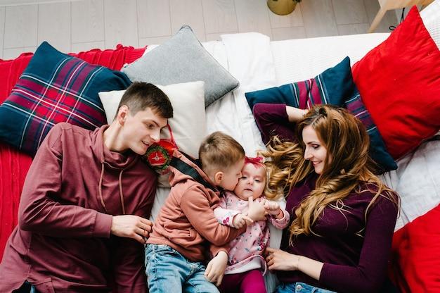 お父さん、お母さんは寝室のベッドで幼い息子と娘を抱きしめます。メリークリスマス。上面図、フラットレイ。家族の休日の概念。閉じる。