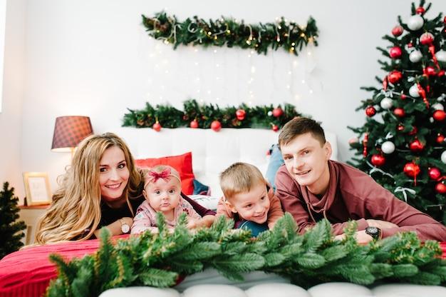 Папа мама обнимает маленького сына и дочку на кровати возле елки рождественский интерьер