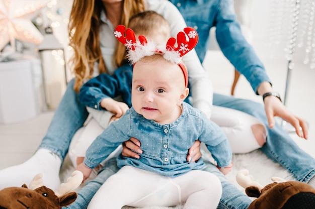 아빠, 엄마는 크리스마스 트리 근처 바닥에 작은 아들과 딸을 안아줍니다. 메리 크리스마스. 크리스마스 장식 인테리어. 가족 휴가의 개념.