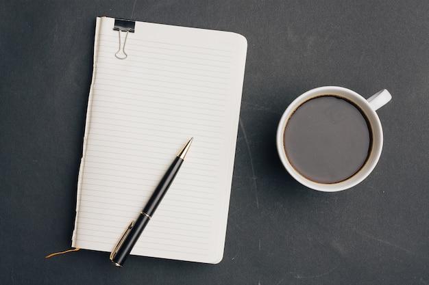 Темный фон чашка кофе офисный блокнот ручка вид сверху