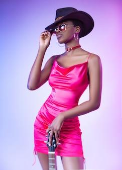 Темнокожая женщина в розовом коротком платье и шляпе с электрогитарой
