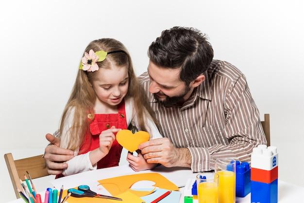 紙のアプリケーションを切り分ける娘と父親