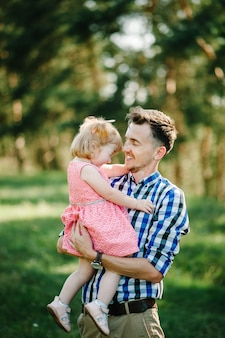 Дочь обнимает отца на природе на летних каникулах. папа и девочка играют в парке во время заката. понятие дружной семьи. крупный план.