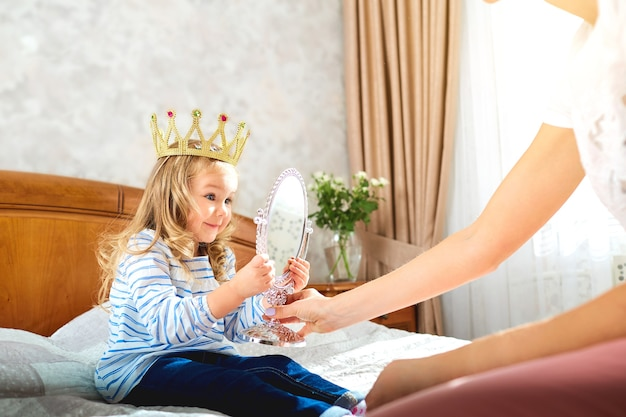 왕관을 쓴 딸은 침대에서 엄마와 놀아요
