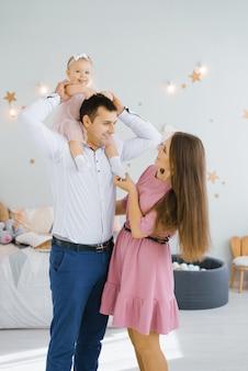 Дочка улыбается и катается на шее отца, а счастливая мама стоит.