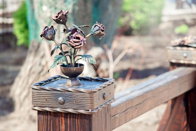 Украшение перил в парке в виде вазы с розами, выполнено методом ковки. красивые кованые железные розы.