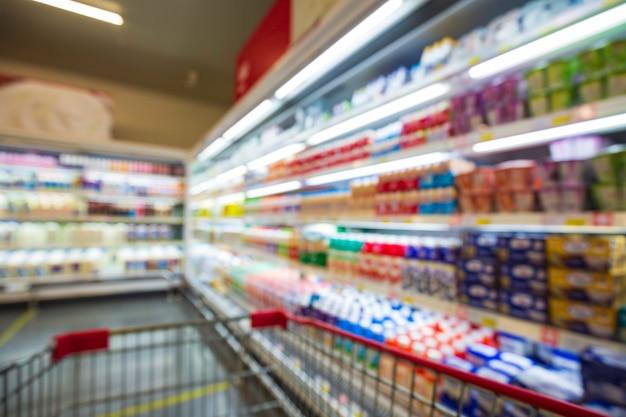 슈퍼마켓의 음료 선반에 있는 음료 우유 식품 구매 카트 쇼핑의 초점을 잃은 흐림.
