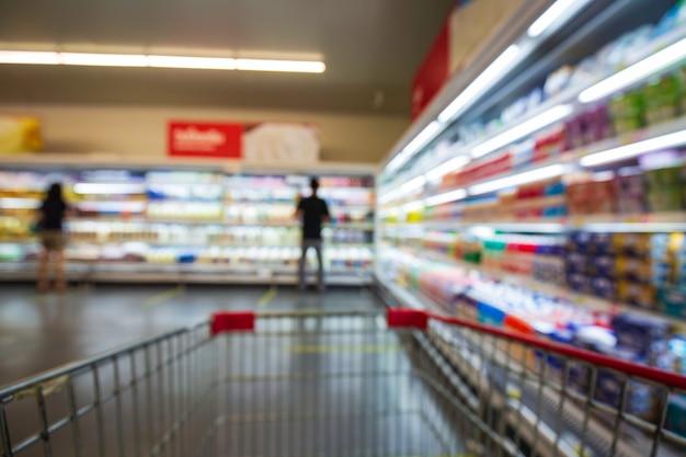 여성 음료 우유 식품 구매 카트 쇼핑의 흐릿한 초점이 슈퍼마켓의 음료 선반에 올려져 있습니다.