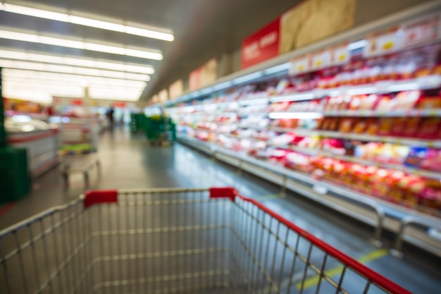 乳製品を使ったカートショッピング肉を購入するスーパーマーケットの焦点がぼけたぼやけ。