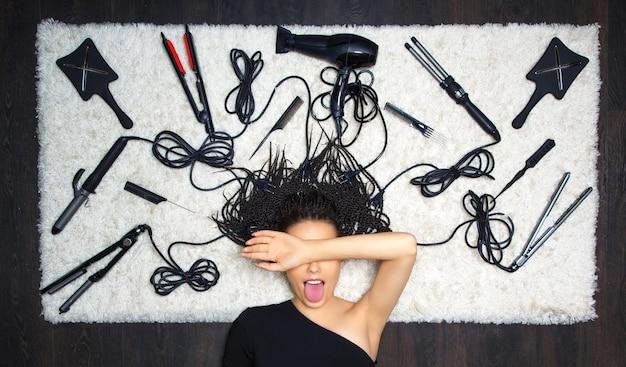 楽しい女の子の床屋は彼女の顔を彼女の手で覆い、彼女の舌を突き出しました。背景には散髪や理髪用のアクセサリーがあります