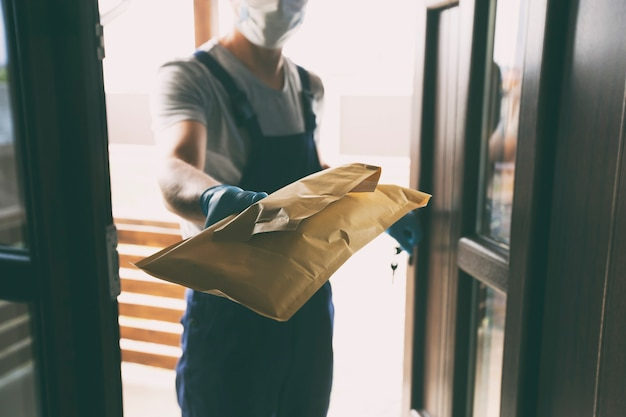 自宅で顧客に小包を渡す配達員