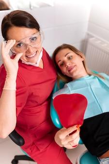 歯科医と彼女の幸せな患者はカメラを見て微笑む。歯科医でのレセプション、健康な歯、幸せな患者、美しい歯。