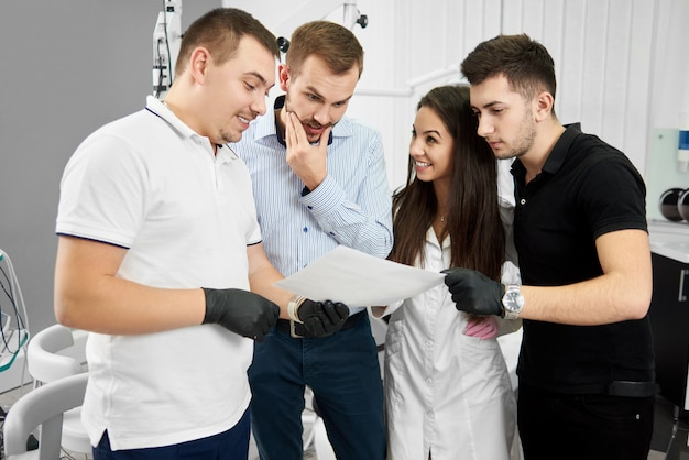 Стоматолог и его помощник показывают пациентам инструкции по уходу за зубами. современные технологии в инновационной клинике