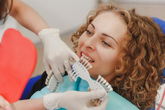 Стоматолог сравнивает оттенок зубов пациента с образцами для отбеливания.