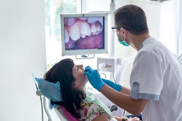 치과 의사가 카메라로 환자를 검사합니다.