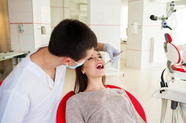 Стоматолог лечит зубы красивой девушки