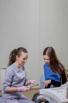歯科医は、美しい女性のための歯のインプラントに適切な色を選択しようとしています。