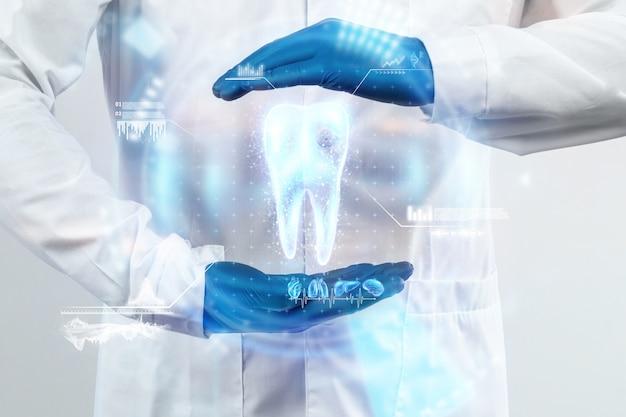 歯科医は歯のホログラムを見て、仮想インターフェイスでテスト結果を確認し、データを分析します。革新的な技術のコンセプト、未来の薬、歯のスナップショット