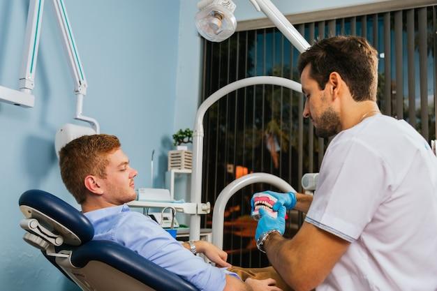 歯科医は彼の若い患者に歯科補綴物を見せます。
