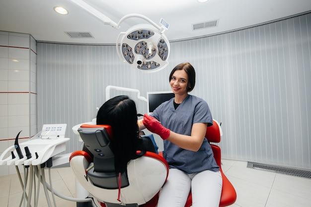 Стоматолог лечит зубы девушки пациенту. лечение зубов
