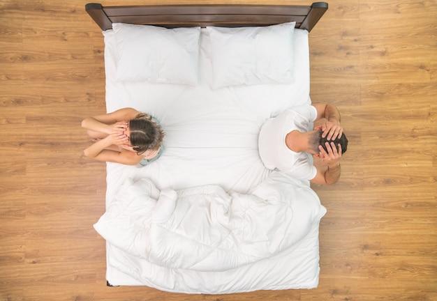В депрессивном состоянии пара держится за голову на кровати. вид сверху