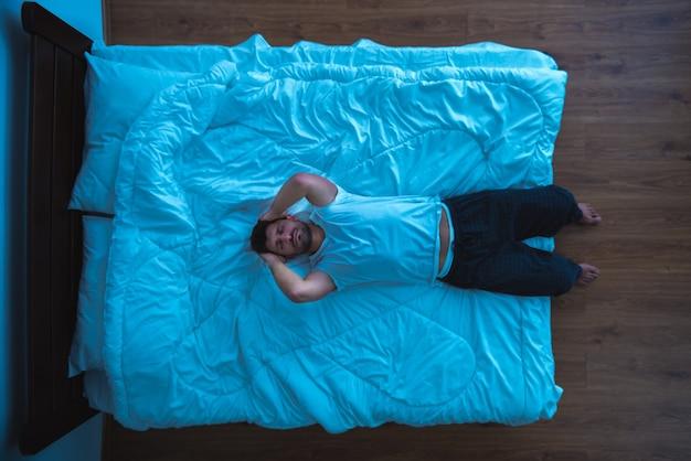 ベッドに横たわっている落ち込んでいる男。上からの眺め、夕方の夜