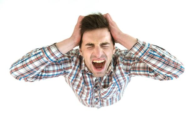 落ち込んでいる男は白い背景に叫びます。上から見る