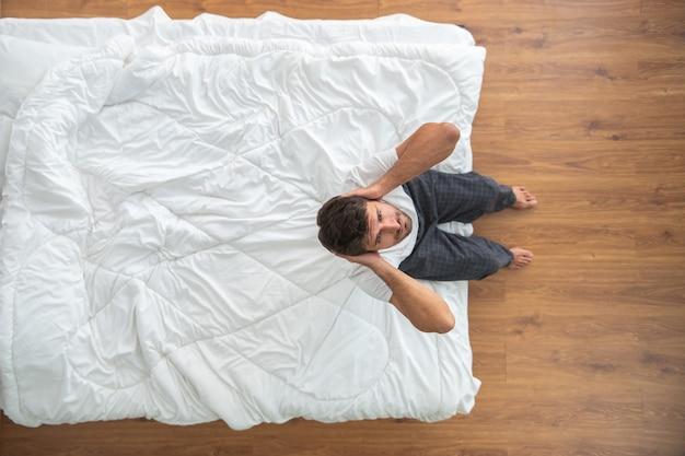 ベッドに座っている落ち込んでいる男。上からの眺め