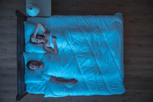 落ち込んでいる女性はベッドに横になりました。夕方の夜の時間。上からの眺め