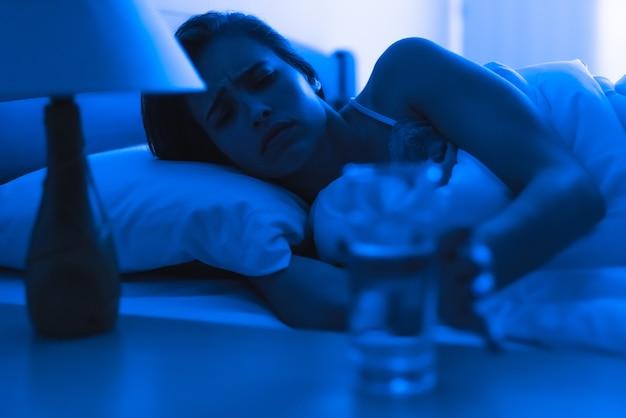 Женщина в депрессии на кровати, держащая укол алкоголя. вечер ночное время