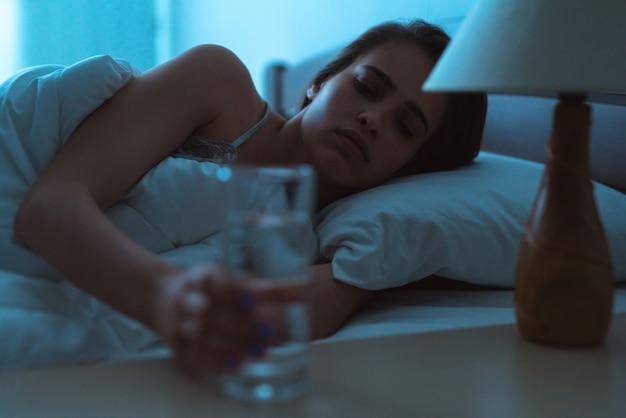 Депрессивная женщина на кровати держит укол алкоголя