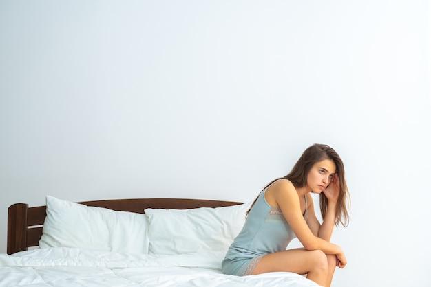 白い背景の上のベッドに座っている落ち込んでいる女性