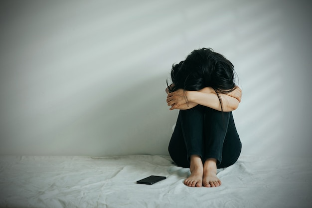 うつ病の女性は膝を抱きしめて泣きます。悲しい女性は彼女のそばに電話をして一人で座っていました。