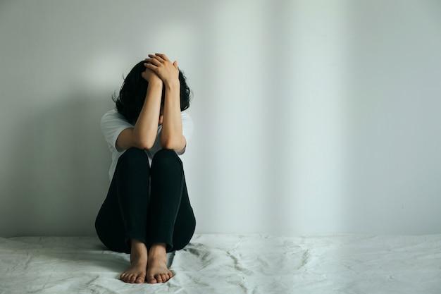 うつ病の女性は膝を抱きしめて泣きます。空の部屋で一人で座っている悲しい女性。