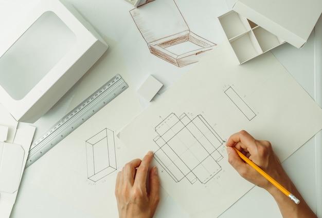 設計者は、段ボール包装のスケッチを描きます。環境に優しい紙箱を作成します。