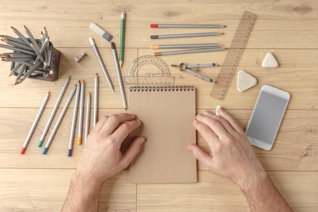 디자이너는 나무 테이블에 노트북에 스케치를 그립니다. 문방구. 위에서 볼 수 있습니다.