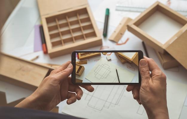 段ボール包装のデザイナーは、スマートフォンブログのプロジェクトスケッチの写真を撮ります。
