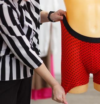 남성 속옷 디자이너는 마네킹에서 완제품의 원단 강도를 확인합니다.