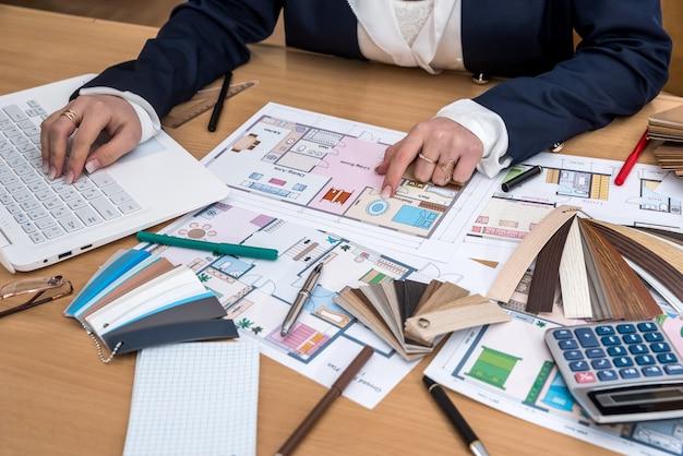 Дизайнер работает в офисе с образцами цветов, ноутбуком и планом здания.