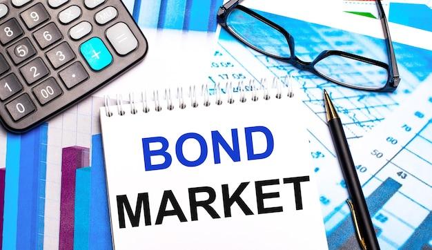 На рабочем столе находятся цветные таблицы, калькулятор, очки, ручка и блокнот с текстом bond market. Premium Фотографии