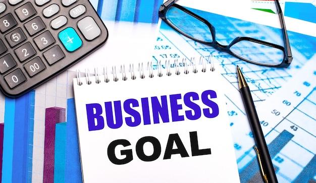 Рабочий стол содержит цветные таблицы, калькулятор, очки, ручку и блокнот с текстом бизнес-цель.