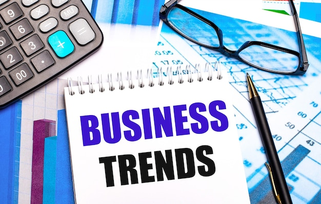 Рабочий стол содержит цветные таблицы, калькулятор, очки, ручку и блокнот с текстом деловые тенденции.