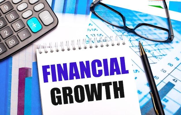 На рабочем столе находятся цветные таблицы, калькулятор, очки, ручка и блокнот с текстом «финансовый рост».