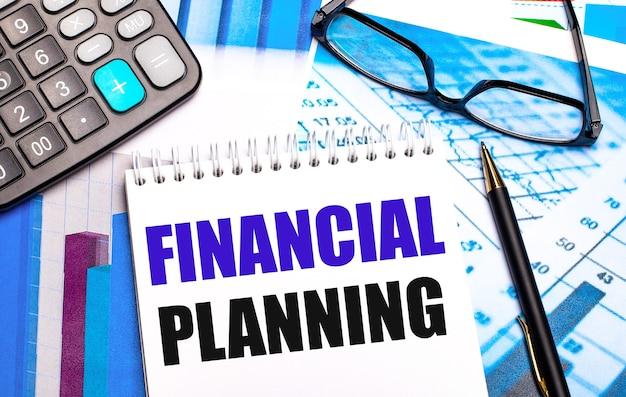 На рабочем столе находятся цветные таблицы, калькулятор, очки, ручка и блокнот с текстом финансовое планирование.