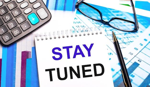На рабочем столе находятся цветные таблицы, калькулятор, очки, ручка и блокнот с надписью stay tuned.